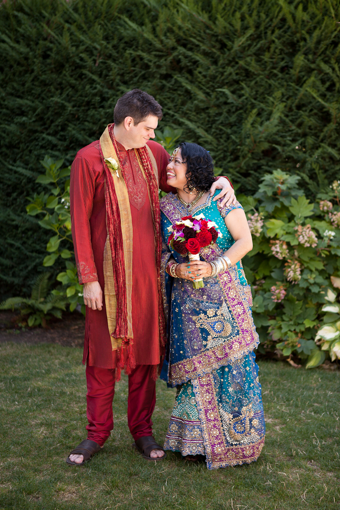 bride-and-groom-in-traditional-indian-outfits-red-teal-purple-gold